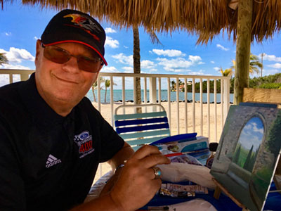 Artist Gilbert Lessard painting one of his art pieces while sitting on a chair on the beach